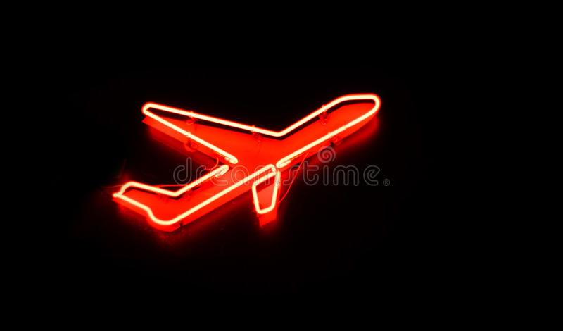 Plane sign at night. Neon shining signboard with plane sign at night stock image