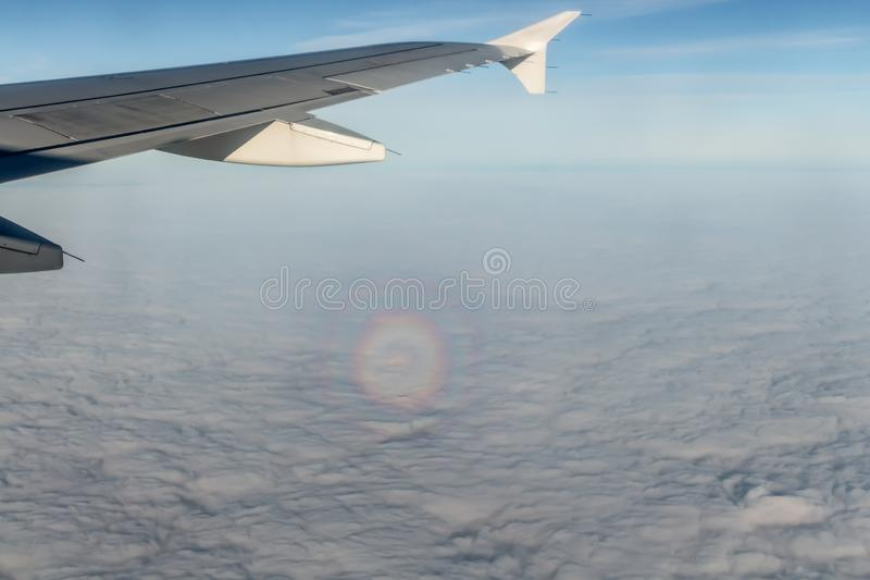 A plane silver wing during a flight over white clouds and a circle Halo optical phenomenon on the photo. A plane silver wing during a flight over white clouds royalty free stock photo