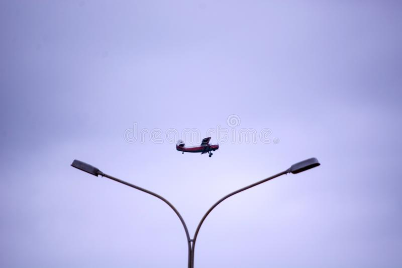 Plane in the sky and above a street lamp royalty free stock photos