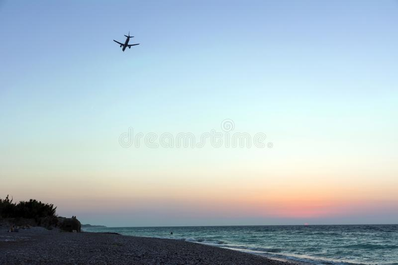 Plane in the sky comes to land over the sea coast at sunset royalty free stock images