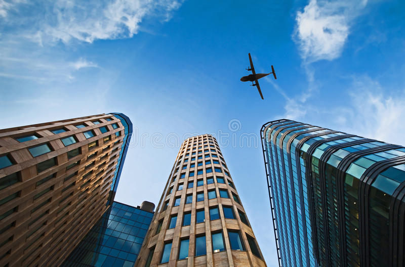 Plane in the sky. Plane over office buildings in blue sky stock photos
