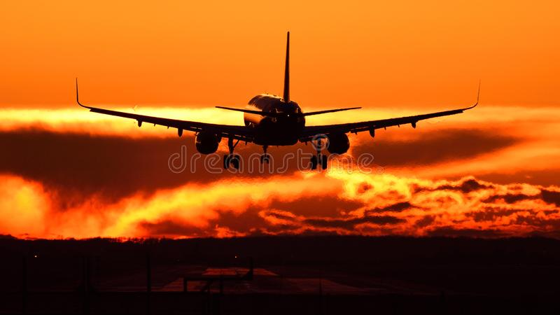 Plane spotting at Otopeni airport during sunset with red sky. And silhouette of a airbus plain royalty free stock image