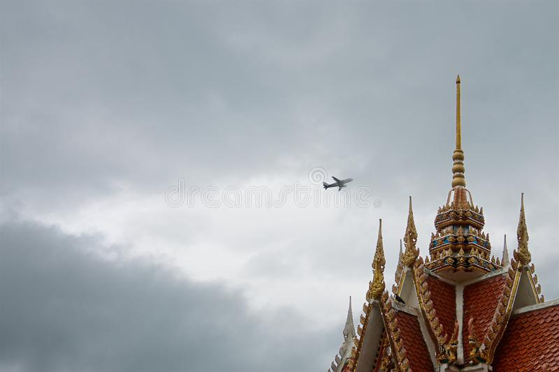 The plane in the storm clouds over the roof of a colorful old Thai temple stock image