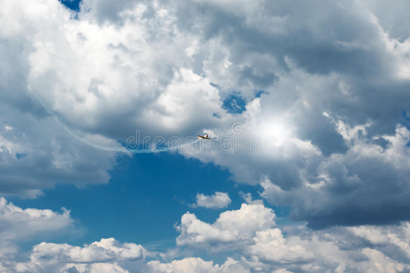 Plane takes off from behind the clouds stock images