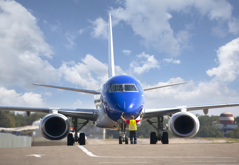 Plane on tarmac in the airport. Guided by ground staff. Taxiing royalty free stock image