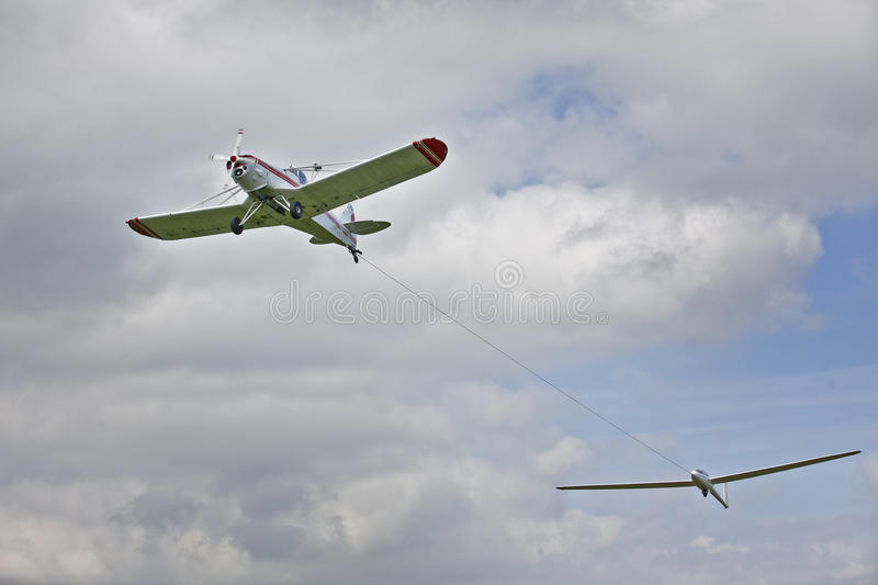 Plane towing glider. Airplane towing glider aircraft with cloudscape background stock photos