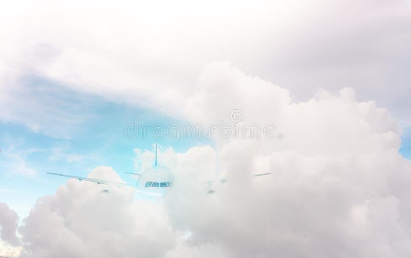 A plane traveling on beautiful white fluffy clouds under vivid and bright blue pastel sky in a suny day royalty free stock photography