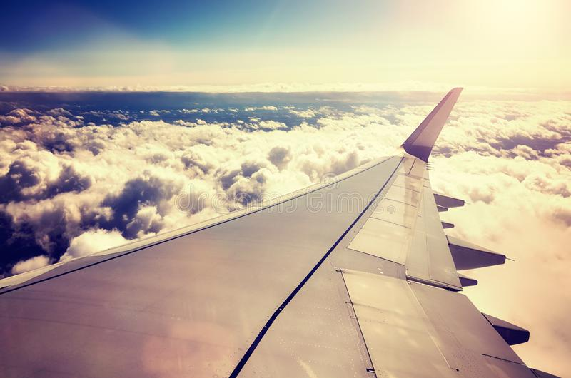 Plane wing above the clouds at sunset. A plane wing above the clouds at sunset seen through a window of an aircraft, color toned travel concept picture royalty free stock images