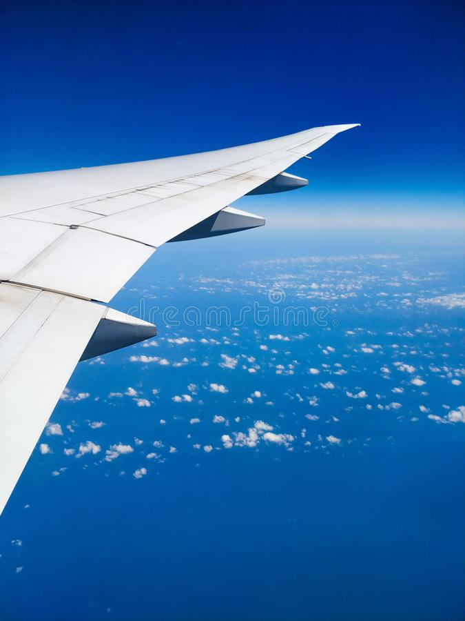 Plane wing above the clouds view clear sky. Aerial view from an airplane of its wing witch copy space stock images