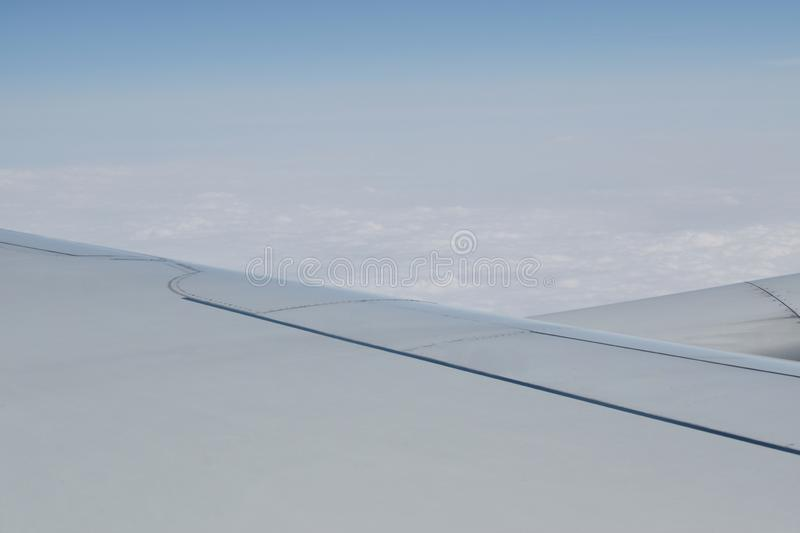 Plane wing and cloud floating on sky through window frame. Plane wing and cloud floating on the sky through window frame royalty free stock photography