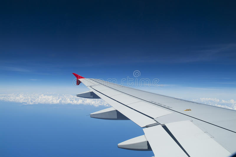 Plane wing. In flight on blue sky background stock images