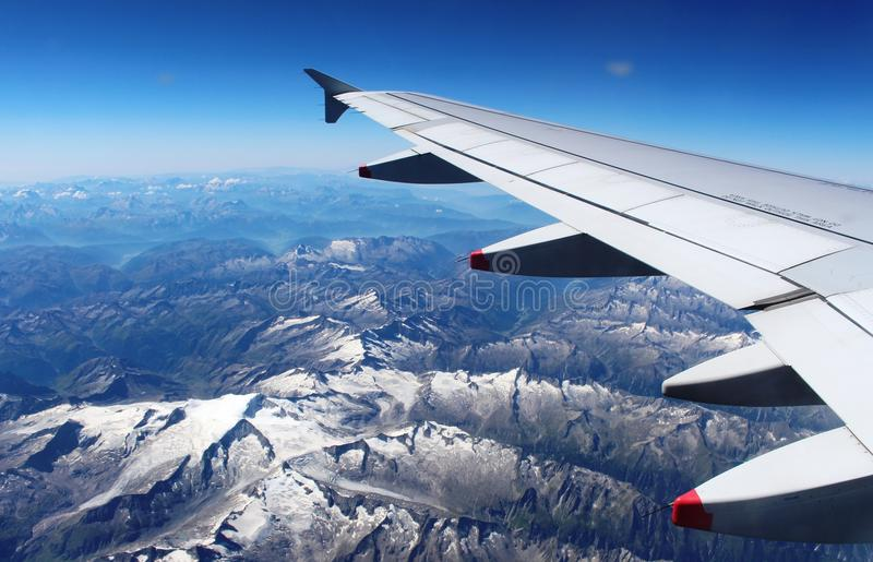 Plane wing over Alps with snow on mountains summer. View down to the Alps from an aircraft with a wing of the plane above the mountains which have a light royalty free stock images