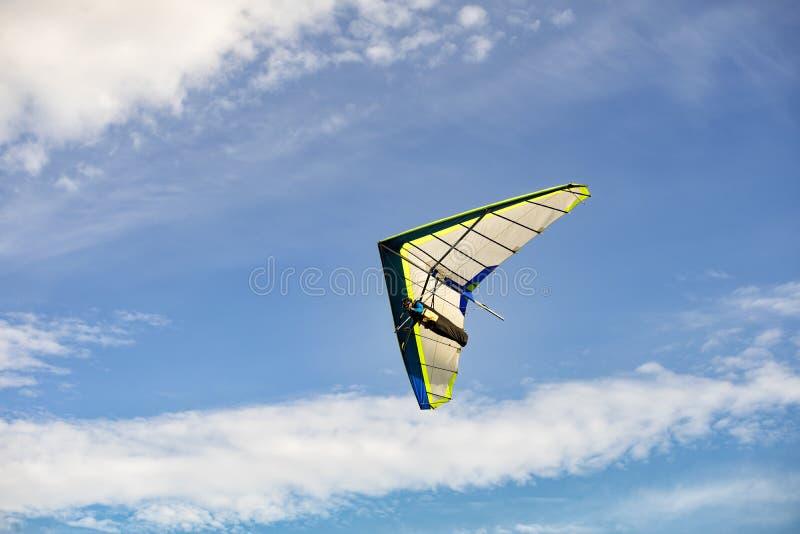 Planeador de caída azul y blanco en vuelo apagado con el cielo azul foto de archivo