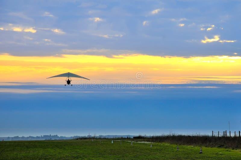 Planeador de caída del motor en la puesta del sol nublada imagenes de archivo
