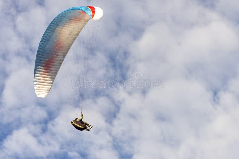 Planeador de Para en la lucha, libraciones en cielo azul nublado imagenes de archivo