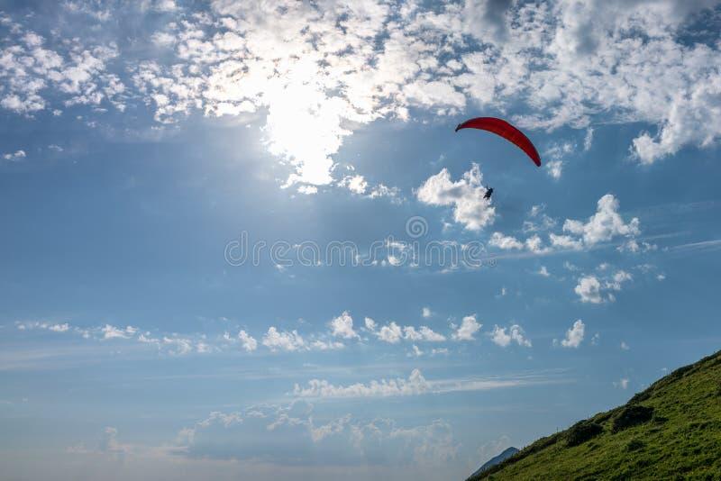 Planeador rojo en cielo nublado azul sobre la montaña verde fotos de archivo libres de regalías