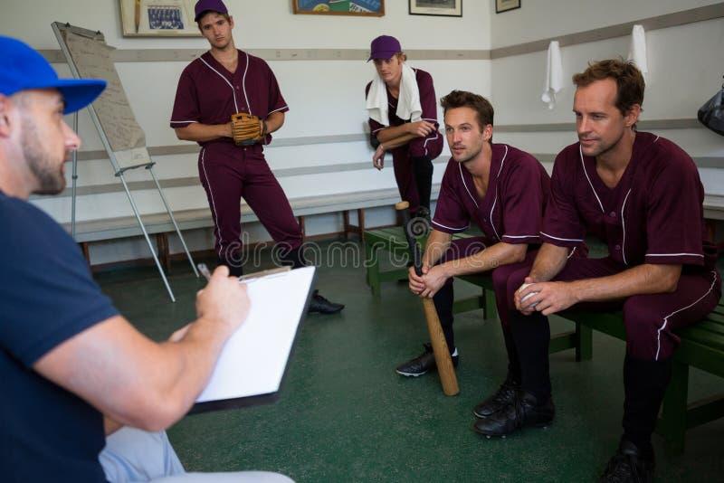 Planeamento da equipa de beisebol com treinador ao sentar-se no banco fotos de stock royalty free