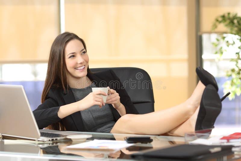 Planeamento relaxado da mulher de negócios no escritório imagem de stock