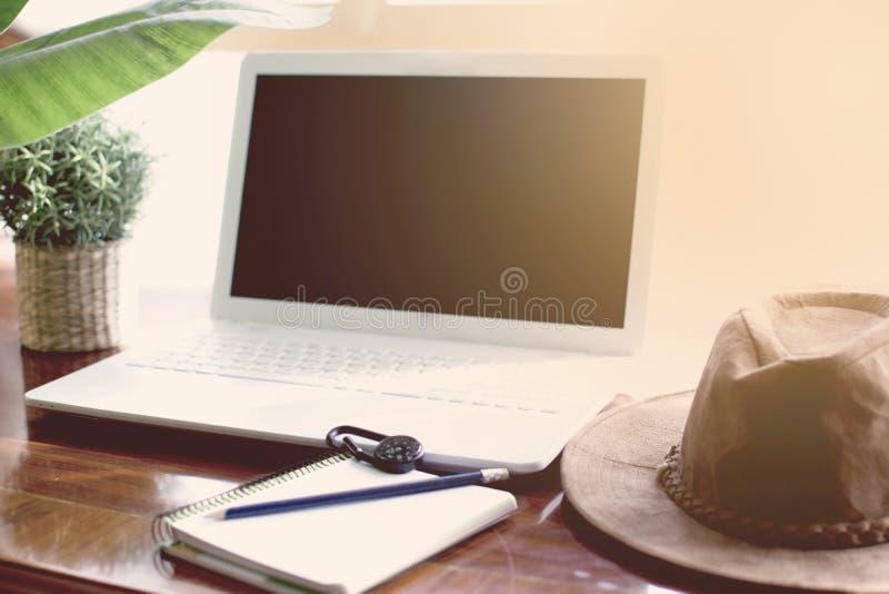 Planeamiento de las vacaciones de la aventura en el ordenador Tabla con el sombrero, la planta, el cuaderno, el lápiz y el compás foto de archivo libre de regalías