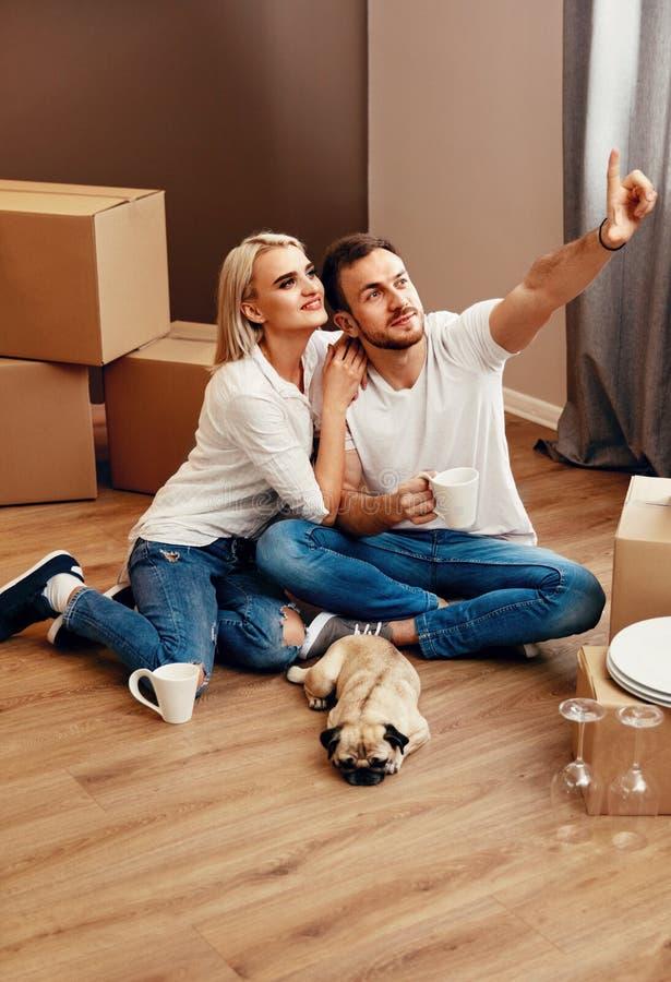 Planeamiento joven de los pares que se mueve en el nuevo apartamento fotografía de archivo libre de regalías