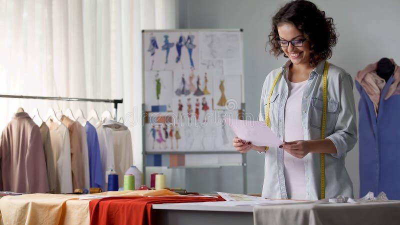 Planeamiento sonriente del diseñador para crear la línea de la ropa según sus propios bosquejos fotos de archivo libres de regalías