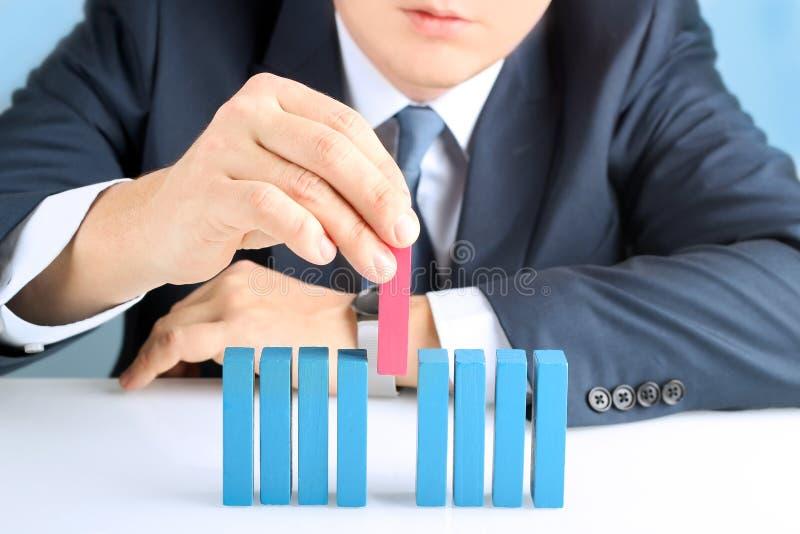 Planear, risco e estratégia no negócio, homem de negócios que coloca o bloco de madeira fotos de stock royalty free