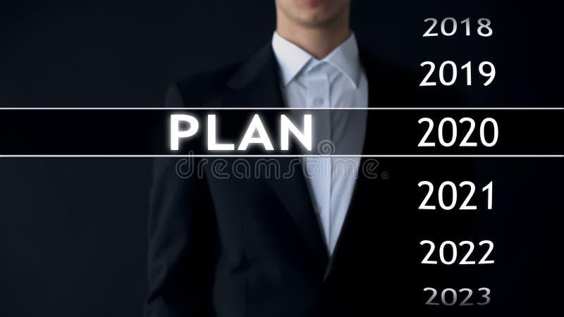 Planee para 2020, hombre de negocios elige el fichero en la pantalla virtual, estrategia financiera foto de archivo