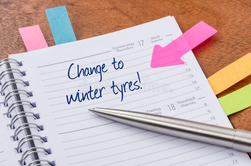 Planejador diário com a mudança da entrada aos pneumáticos do inverno imagem de stock