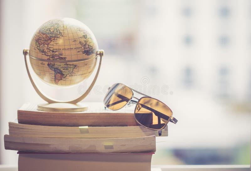 Planejando a viagem seguinte: Globo e óculos de sol diminutos em uma pilha de livros imagens de stock royalty free