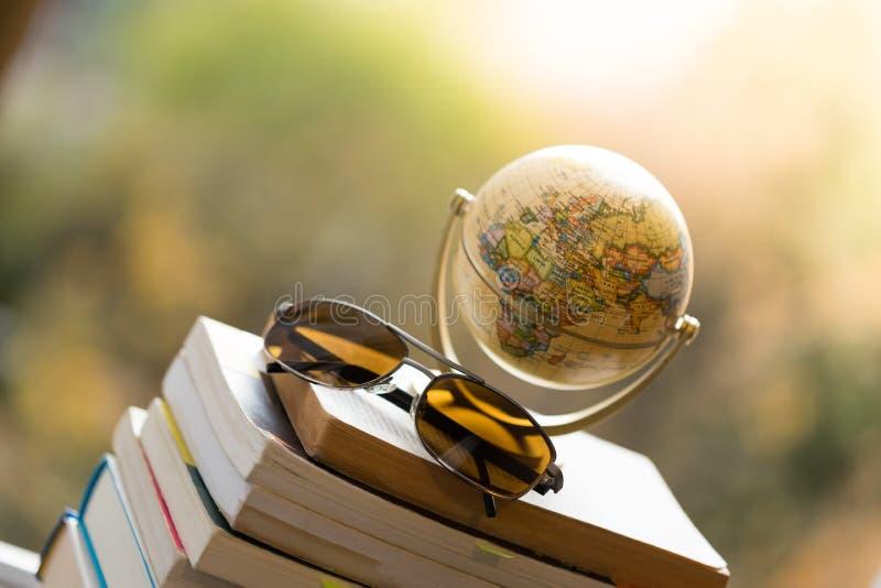 Planejando a viagem seguinte: Globo e óculos de sol diminutos em uma pilha de livros foto de stock