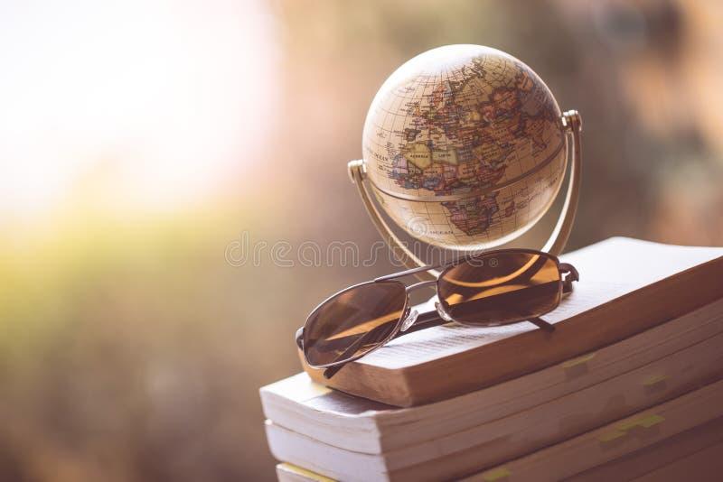 Planejando a viagem seguinte: Globo e óculos de sol diminutos em uma pilha de livros foto de stock royalty free