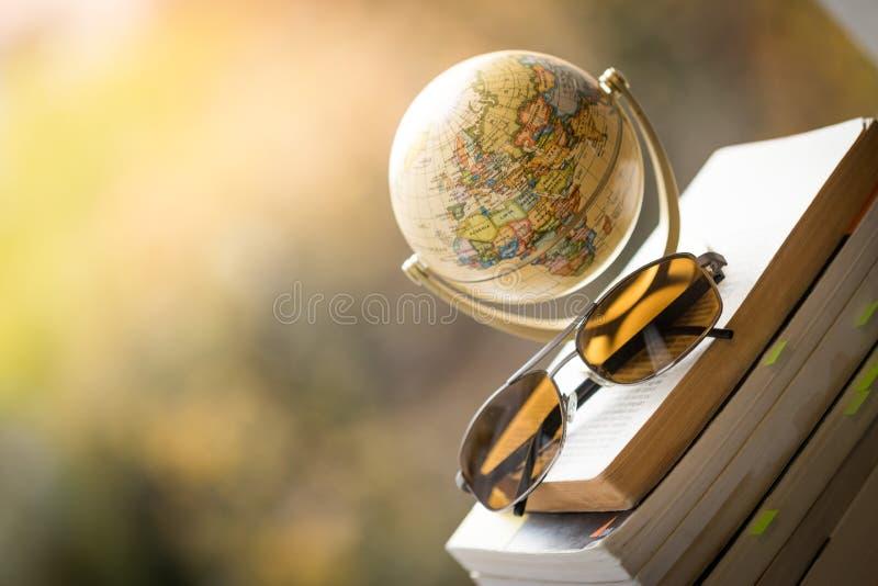Planejando a viagem seguinte: Globo e óculos de sol diminutos em uma pilha de livros fotografia de stock royalty free