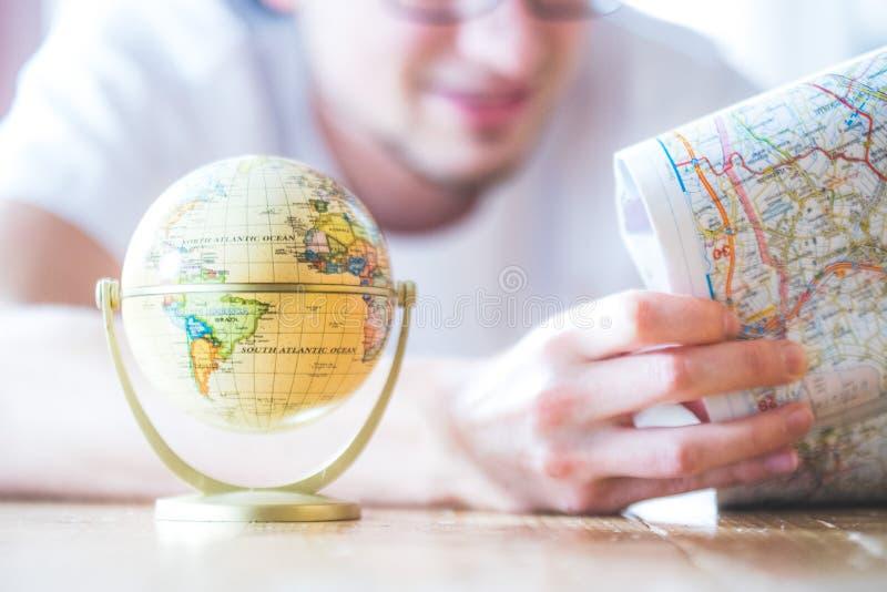 Planejando a viagem seguinte: Homem com mapa e globo diminuto no assoalho foto de stock