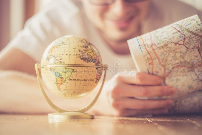 Planejando a viagem seguinte: Homem com mapa e globo diminuto no assoalho imagens de stock royalty free