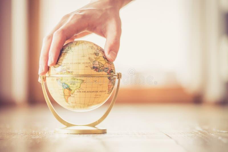 Planejando a viagem seguinte: o globo diminuto no assoalho de madeira, entrega o toque dele fotografia de stock royalty free