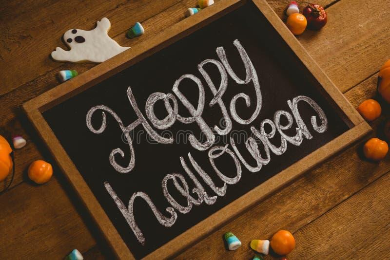 Planen Sie mit glücklichem Halloween-Text durch Süßigkeiten auf Holztisch stockfotografie