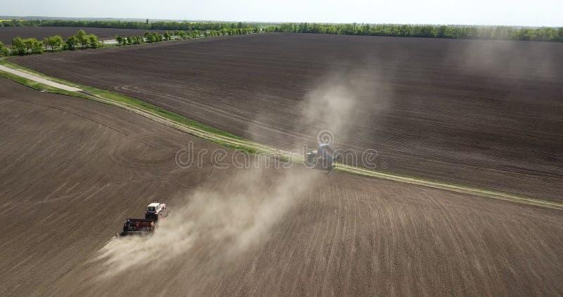 Planera arbeten i fältet, en traktor med ett harv, odling, jordförberedelse för jordbruks- arbeten Sikt från en fågel arkivbilder