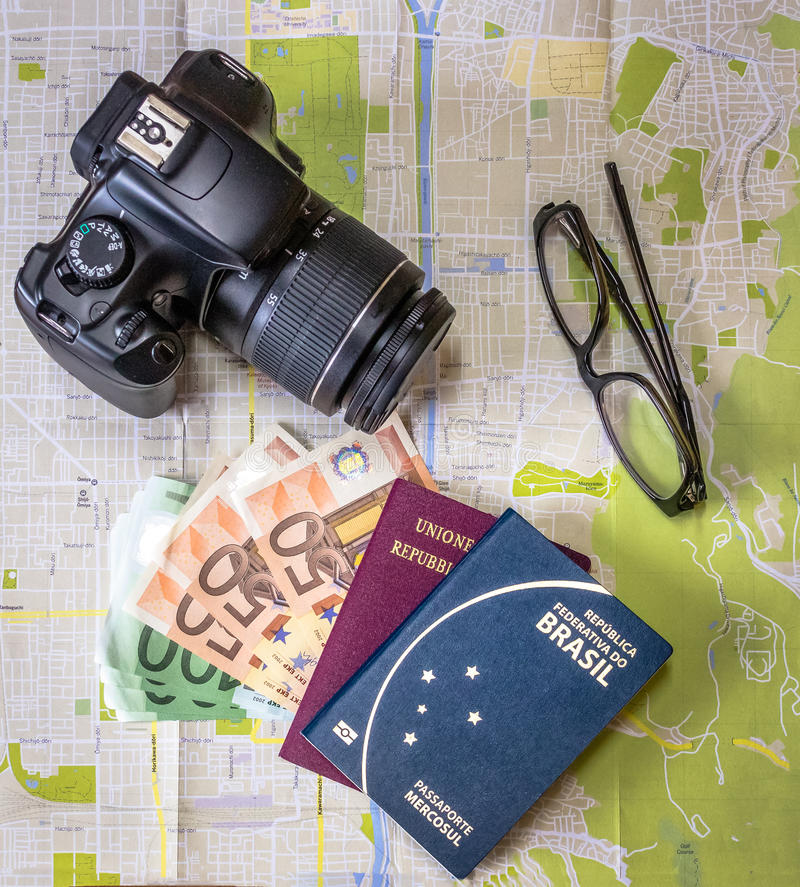 Planera brasilianska och italienska pass för en tur - på stadsöversikt med euro fakturerar pengar, kameran och exponeringsglas royaltyfri foto
