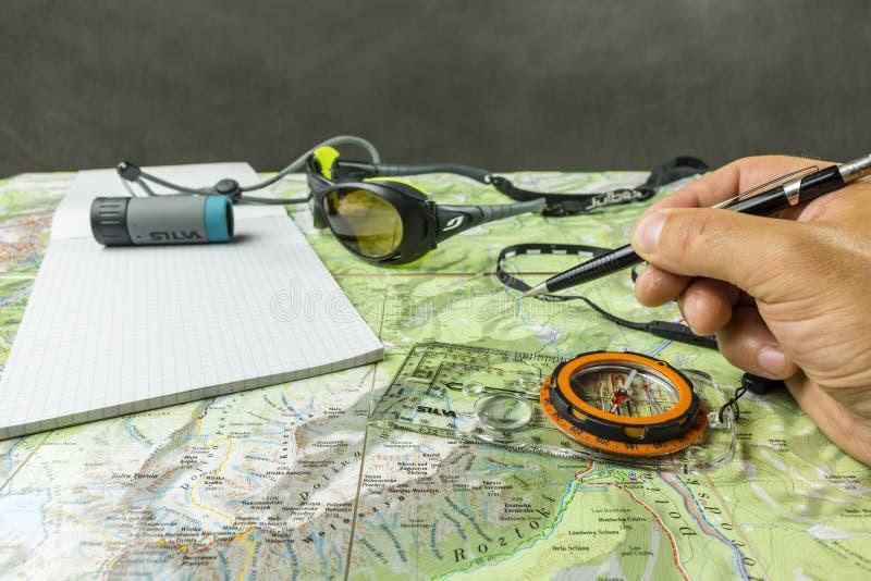 Planera och bestämma riktningen av en tur på en turist- översikt genom att använda en kompass arkivbilder