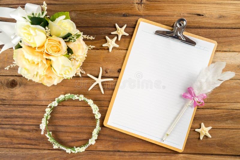 Planera papper med pennan, rosa huvudbindel, tiara, bukett, sjöstjärna royaltyfria foton