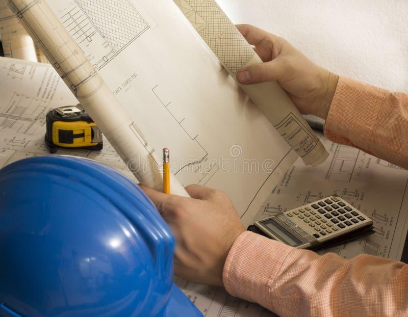 Planes arquitectónicos del ingeniero-arquitecto de la construcción que revisan planes con el metro, el casco, la calculadora y el foto de archivo