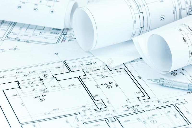 Planes arquitectónicos y lápiz del proyecto en el lugar de trabajo del arquitecto fotos de archivo