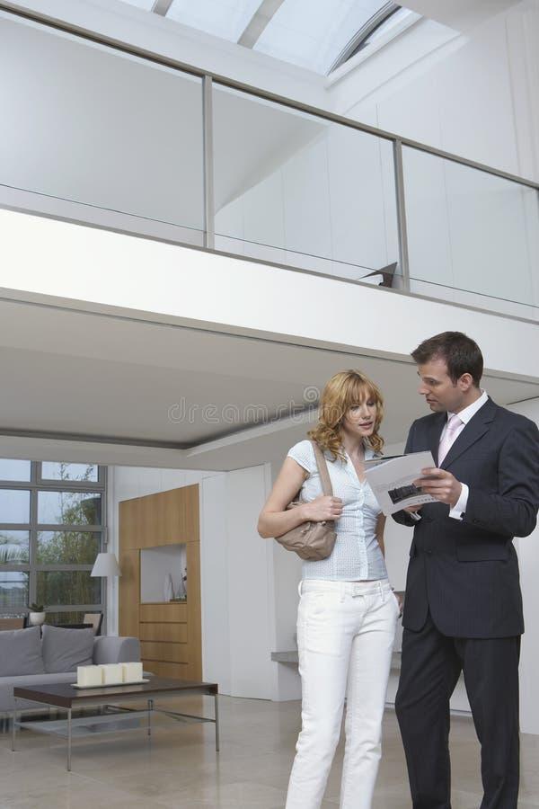Planes de la casa de Showing Woman New del agente inmobiliario fotografía de archivo libre de regalías