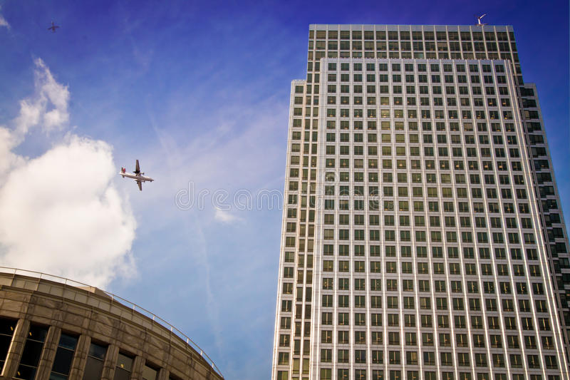 Planes flying by One Canada Square, London. Two planes flying by the One Canada Square skyscraper in the financial district of Canary Wharf, Docklands, London royalty free stock photos