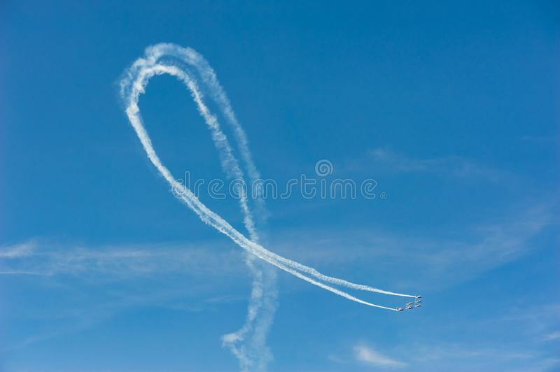 Planes in formation doing a loop with white smoke trail in blue stock images