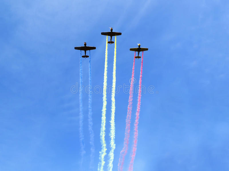 Planes with smoke trail. Planes in formation making Romania Flag from colored smoke trials, against blue sky royalty free stock photography