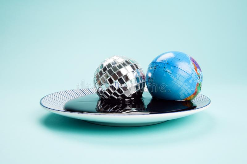 Planet earth and a disco ball drowned in an oil spill. An antistress ball representing the planet earth near a disco ball drowned in an oil spill. Minimal still stock image