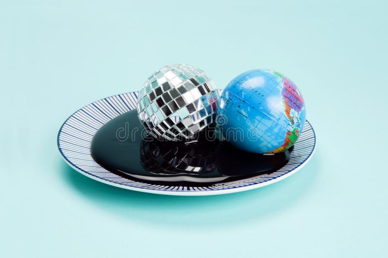 Planet earth and a disco ball drowned in an oil spill. An antistress ball representing the planet earth near a disco ball drowned in an oil spill. Minimal still stock photos
