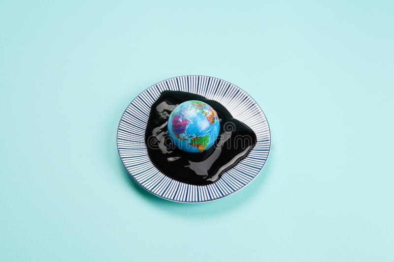 The planet earth drowned in an oil spill. An antistress ball representing the planet earth drowned in an oil spill. Minimal still life color photography stock image