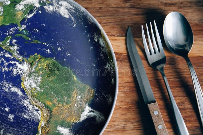 The planet Earth plate with a fork and knife on a wooden background. World hunger concept. Feed the world royalty free stock images